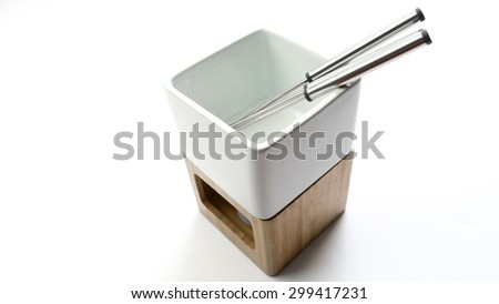 Ceramic porcelain candle holder and fondue compartment, stainless steel stick and wooden fondue set for four. Isolated on white background. Slightly de-focused and close-up shot. Copy space.