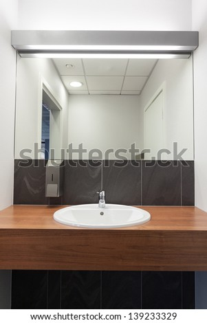 Ceramic sink dropped in a wooden counter - stock photo