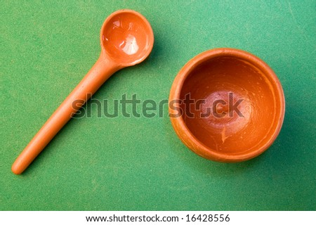 Ceramic spoon with plate isolated on green - stock photo