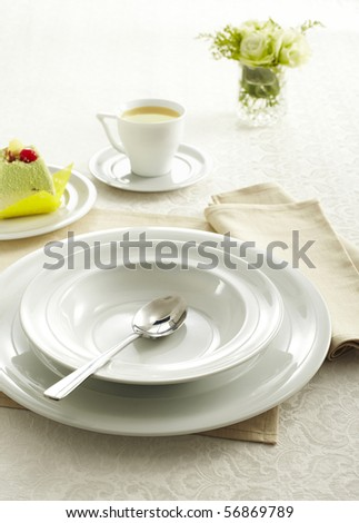 Ceramic tableware and Soupspoon - stock photo