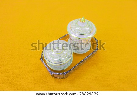 Ceramic tea set in white gold pattern on a orange background. - stock photo