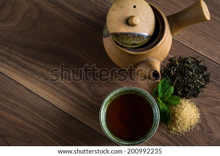 Ceramic teapot, cup of black tea with mint leaves and brown sugar on wooden table with copy space - stock photo
