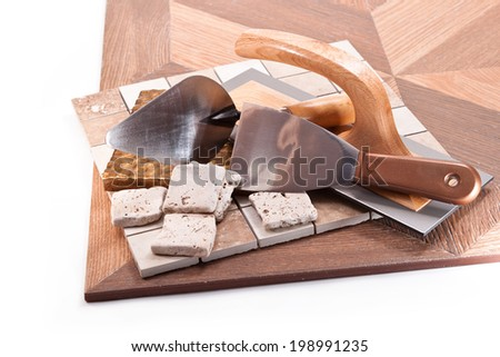 Ceramic tile, marble and stone, trowel, spatulas on a white background - stock photo