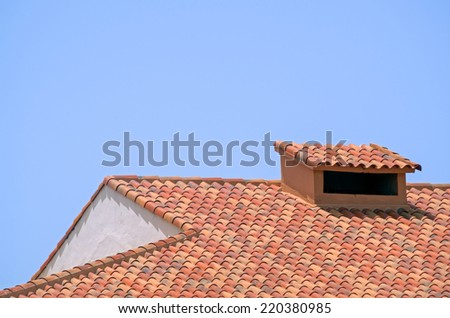 Ceramic tile roof with chimney and white wall, blue sky as background - stock photo