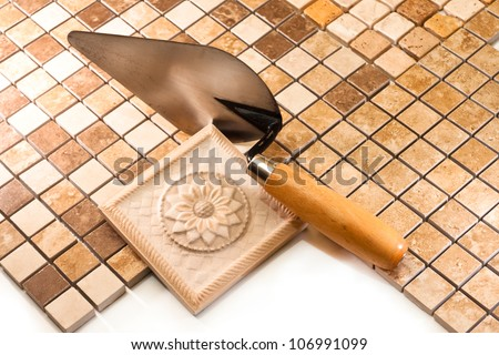 Ceramic tiles of different colors, shapes and trowel for tiler - stock photo