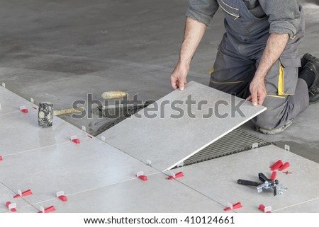 Ceramic Tiles. Tiler placing ceramic wall tile in position over adhesive with lash tile leveling system - stock photo