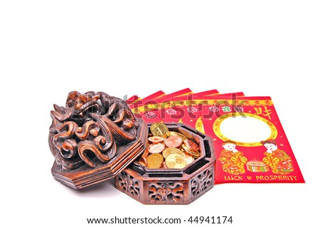 Ceramic vessel full of coins and chinese lucky money envelopes. - stock photo