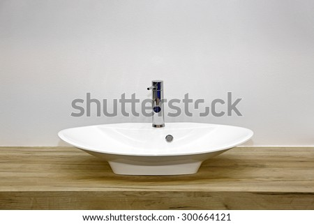 Ceramic Wash Basin at Wooden Counter in Contemporary Bathroom - stock photo
