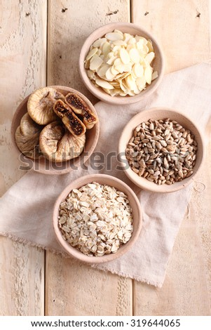 cereal and grain in wooden bowl- oat, fig, sunflower seed and almond - stock photo