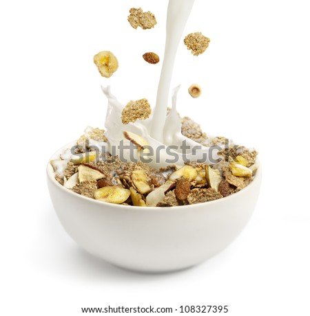 cereal and milk pouring into a white bowl - stock photo