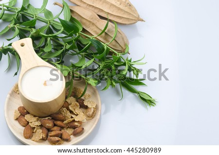 Cereal and nuts with milk in the wooden small bowl on white gourd - stock photo