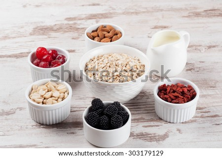 cereal and various delicious ingredients for breakfast and white wooden background, horizontal - stock photo