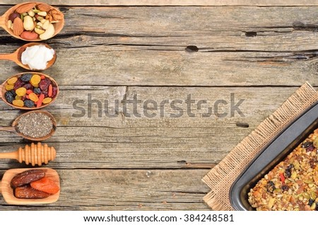 Cereal and various delicious ingredients for breakfast - dried fruits, nuts and honey on wooden table. Healthy breakfast concept. Ingredients for homemade granola. Copyspace background. Top view. - stock photo