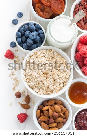 cereal and various delicious ingredients for breakfast, vertical, top view, close-up - stock photo