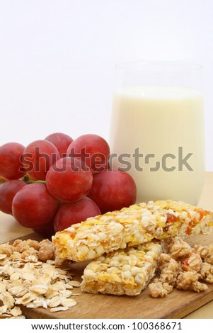 Cereal bar with grapes and milk. - stock photo