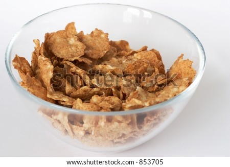 Cereal flakes in a glass bowl on white background - stock photo
