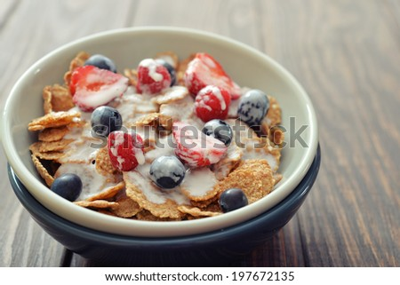Cereal flakes with fresh berries and yogurt in bowl on wooden background