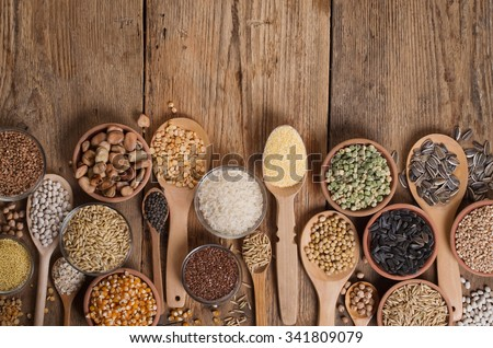 Cereal grains , seeds, beans on wooden background.