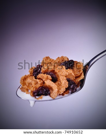 Cereal in spoon with fruit and milk - stock photo