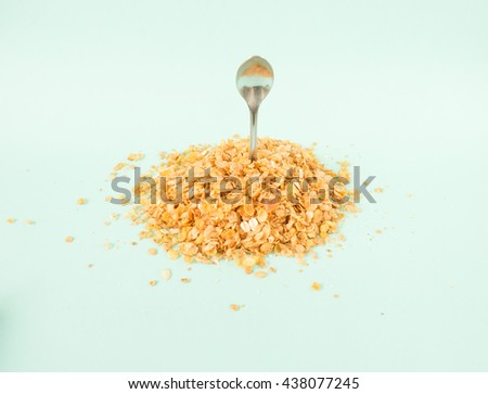 Cereal lover concept. Pile of  cereal with raisins and spoon isolated on blue background. - stock photo