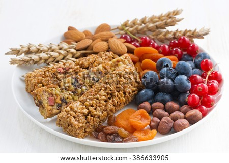 cereal muesli bars, fresh and dried fruit on a plate, horizontal - stock photo