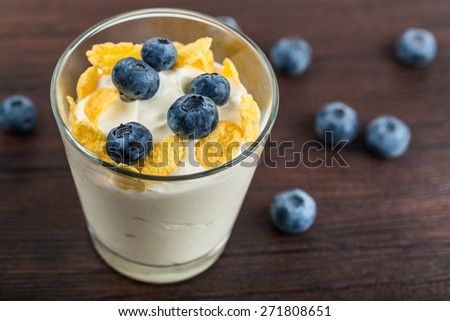 Cereal. Yogurt with granola and fresh blueberries, in glass bowl over old wood background. Vintage effect. - stock photo