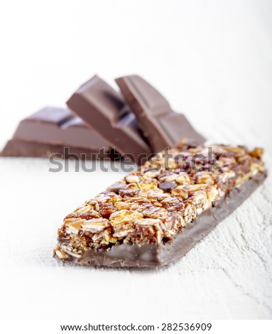 Cereals bar with chocolate on white wooden background - stock photo