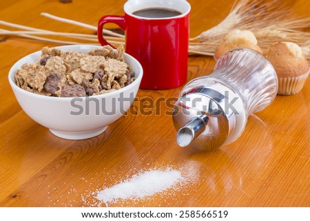 Cereals, coffee, cupcake and sugar spilled on the table - stock photo