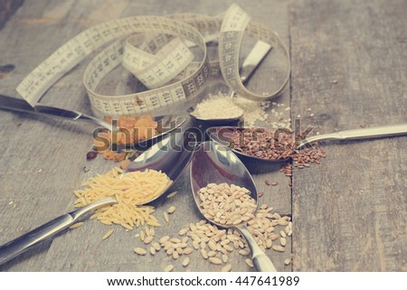 Cereals collection in metal spoons and metre on old rustic table