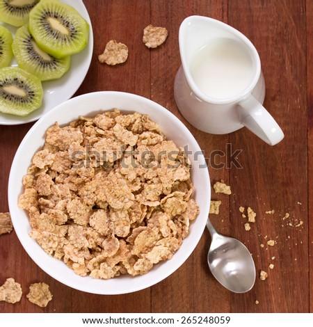 cereals in white bowl, milk and kiwi - stock photo