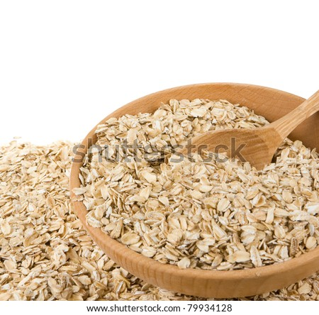 cereals oat flake in wood plate isolated on white background