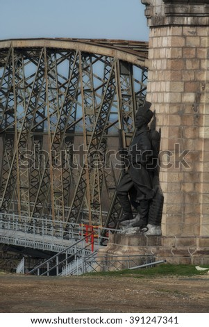 Cernavoda, Romania - March 06, 2016. Cernavoda Bridge.  Statue of a romanian soldier, from first world war, watching the head of bridge. Dobrogea. Romania.
