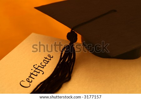 certificate printed on a yellowish grainy textured paper and a black graduation cap, on yellow - orange background - stock photo