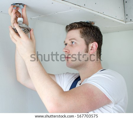 Certified electrician installing light bulb - stock photo