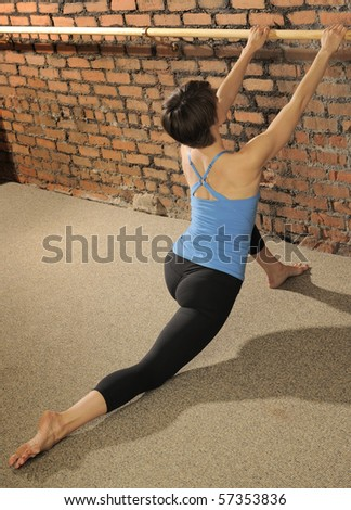 Certified Pilates instructor demonstrates difficult stretching workout at ballet barre in exercise studio - stock photo