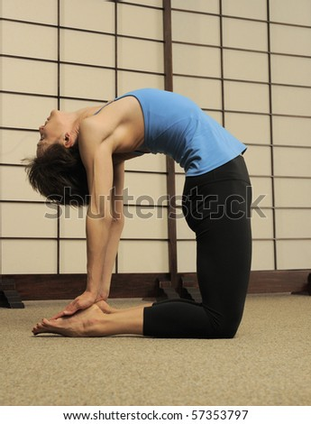 Certified Pilates instructor demonstrates difficult stretching workout in exercise studio. - stock photo