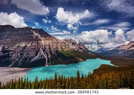 Cerulean glacial lake, nested in the mountains, pine trees and rocky mountain top, playful clouds - stock photo