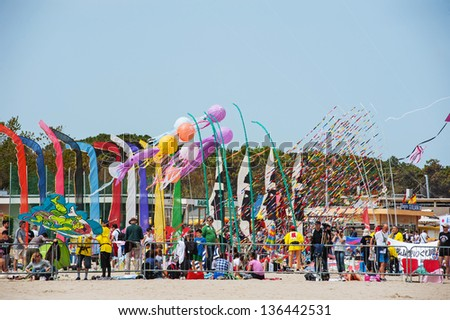 CERVIA, ITALY - APRIL 25: People enjoying International Kite Festival on April 25, 2013 in Cervia. This Festival brings together kite flyers from all over the world every year since 1981. - stock photo