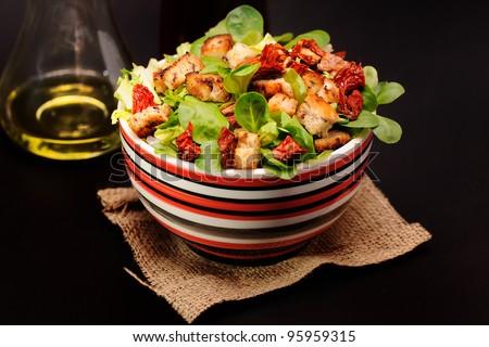 cesar salad on black background with bottle of olive oil - stock photo