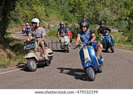 "CESENA, ITALY - JUNE 26: group of bikers riding a vintage italian scooters Vespa on the hills during the scooter rally ""I colli di Romagna"" on June 26, 2016 in Cesena, FC, Italy"