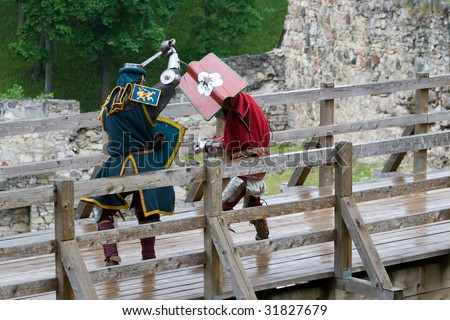 CESIS, LATVIA, June 7: Knight sword fight on wooden bridge during  the medieval festival Livonia. 1378. Held in Cesis, Latvia on June 7, 2009