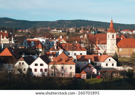 Cesky Krumlov - the famous Czech city, part of the World Heritage, UNESCO. The red roofs of the city and the tower on the background of bright blue sky - stock photo