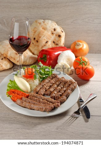 Cevapcici, a small skinless sausage cooked on the barbecue and served with: Lepinja bread, pickled red capsicum and Kajmak cheese. This dish is popular all over the Balkans, with tourists and locals.