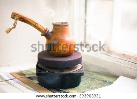 Cezve of coffee on a small stove on a windowsill near the old window - stock photo