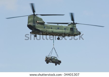 CH-47 Chinook helicopter carrying 4x4x off-road mercedes - stock photo
