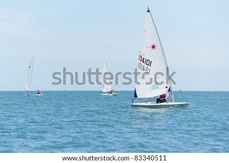 CHA-AM THAILAND - AUGUST 23: An unidentified Laser sailboat competes during Day 2 of the 2011 Hua Hin Regatta on August 23, 2011 at Dusit Thani Resort & Spa Hua Hin in Cha-Am, Thailand - stock photo