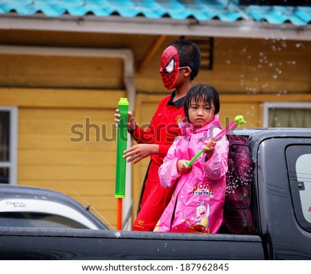 Chachoengsao Province 13 April 2014: a young Thai little girl wearing colorful clothes celebrate Songkran water festival splashing water with water spray guns on the street in cities of Thailand