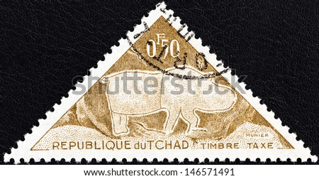 "CHAD - CIRCA 1962: A stamp printed in Chad from the ""Prehistoric petroglyphs"" issue shows Rhinoceros, circa 1962.  - stock photo"