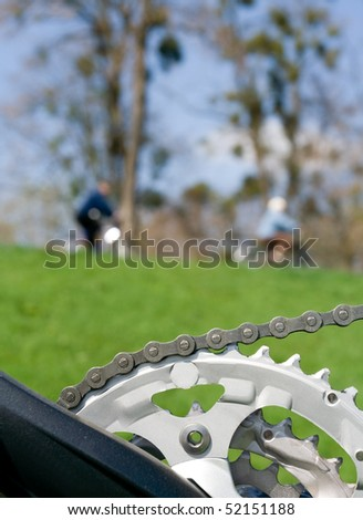 Chain and bicycle gear over blurred people riding bicycles