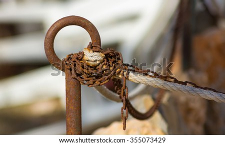 chain and rope detail in a rusty ring - stock photo